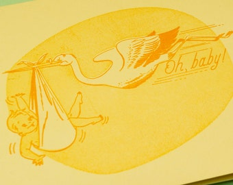 Oh Baby Letterpressed Greeting Card in Orange and Yellow Ink on Light Yellow Paper Featuring an Image of a Stork Bird Printed in Cleveland