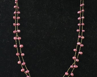 Very long necklace of offset mauve colored freshwater pearls and french cut seed beads.