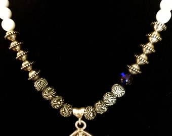 Handmade Necklace made with a strand of beautiful beads, featuring a carved metal Buddha Pendant