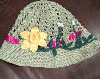 By KnottedwLove Designs. Bucket hat in green with yellow flower.