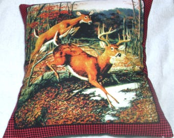 Stag and deer leaping over a fallen tree in a forest cushion