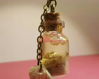 Glass vials with shell pendant on bronze chain