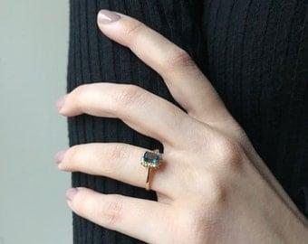 14 karat yellow gold diamond and emerald cut blue topaz ring