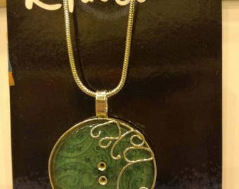 Green button with silver scrollwork