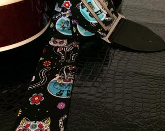 Day of the dead kitties guitar strap -- colourful cartoon skeleton cats on a black background