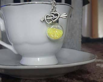 Super cute miniature yellow glitter sparkles inside a mini glass jar with silver heart charm necklace