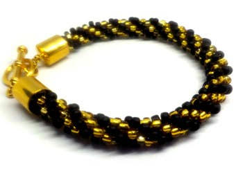 Elegant  black and gold bracelet beaded  on a Kumihimo braid