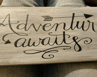 Adventures Await board sign