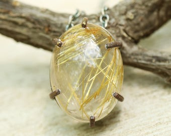 Rutilated quartz pendant necklace in silver bezel and brass prong setting