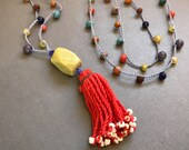 Crocheted long multicolored necklace with faceted serpentine and dancing red tassel