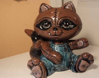 Hand painted ceramic quilted look raccoon in blue jean overalls