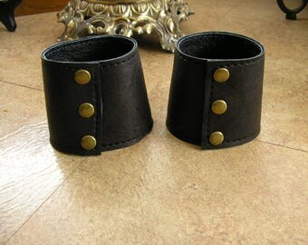 "Leather cuff bracelet in Black distressed leather with brass tone snaps, 7"" at wrist  2 1/2"" wide"