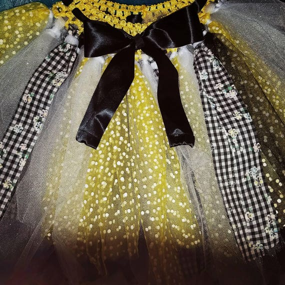 Yellow, white and black tutu with daisy accents. Fits most kids up to 6 yrs old