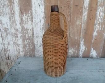 Vintage wicker covered demijohn , wrapped brown bottle