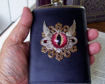 Dragon Eye Emblem Flask (F607) 8 ounce, Black Leather, Hand Painted Glass Eye, Brass Stamping, Silver Wings, Swarovski Crystals