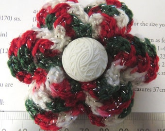 Irish crochet flower brooch in variegated red, green and white wool with white button centre