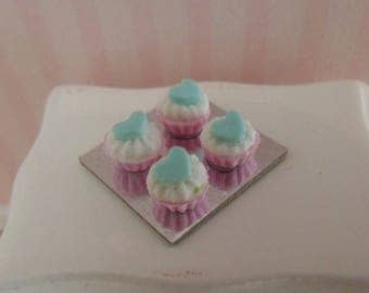 4 cupcakes on a silver plate