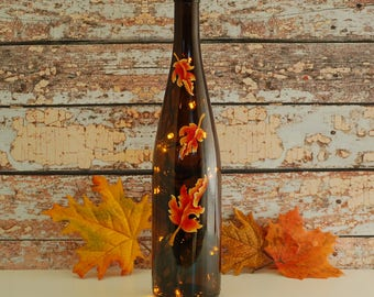 Wine bottle light with hand painted autumn leaves and gold lights