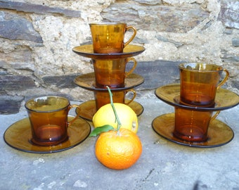 Six medium sized Duralex French coffee/tea cups and saucers amber glass seventies