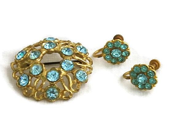 Blue rhinestone brooch and earrings in filigree gold metal setting, open metal work, screw back earrings, circa 1950s