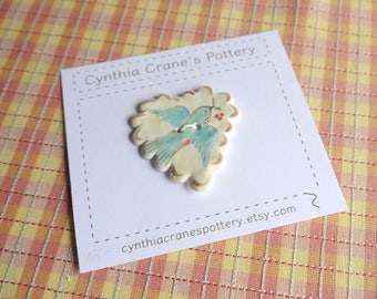 Ceramic Button, Large Heart with Scalloped Edge Detail, Painted Blue Bird on Yellow Background