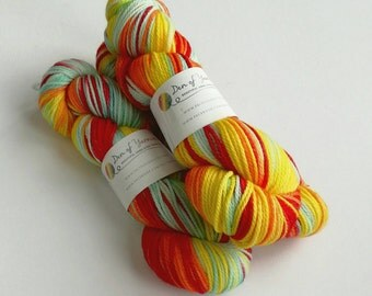 Hand dyed wool yarn. Phoenix Rising - 100g of superwash merino aran weight yarn. Orange, yellow, red, pale blue. Knitting, crochet. UK dyer.