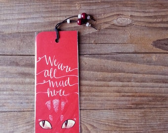 Alice in wonderland: cheshire cat, red bookmark, with handwritten calligraphy