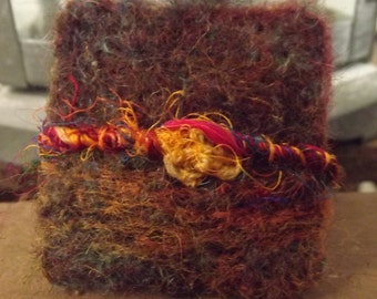 Pretty needle felted brooch created using natural wool and sari silk inspired by summer meadows