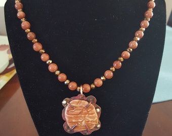 Gold-stone bead necklace with crystals beads and a copper and silver pendant that has a fragment of a shell as a focal point