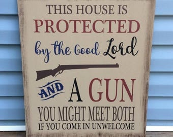 This house is protected by the Lord and a gun- painted wood sign