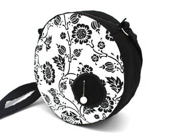 Black round shoulder bag enhanced with white cotton patterned with black flowers