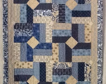 Quilt made of blues and beiges in a swirling  Pattern.  Very modern for that modern baby.