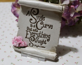 A quaint gift scroll handmade from clay with the  quote A Smile Is A Curve That Sets Everything Straight by Tags and Tokens Fundraising