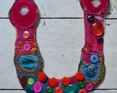 Beautiful embroidered and stitched textile necklace in pinks, oranges and greens, decorated with vintage buttons and pom poms