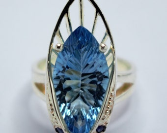 Silver ring set with a Blue Topaz and blue sapphires in tilings