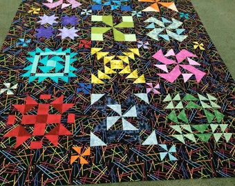 Scrappy quilt top with black knitting needles background