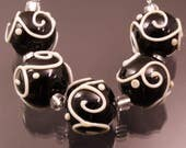 black rounds with ivory scrollwork and dots