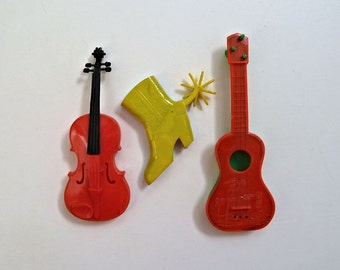 Three Different Vintage Plastic Music Toys Guitar Cowboy Boot Whistle Violin Harmonica