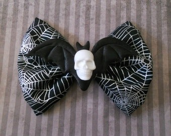 skull and bat wings on a spider Web hair bow clip pastel goth