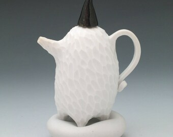 Carved white porcelain teapot on pillow