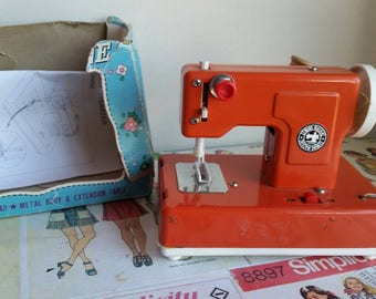 Vintage made in Japan red enamel metal toy sewing machine with partial box and instructions