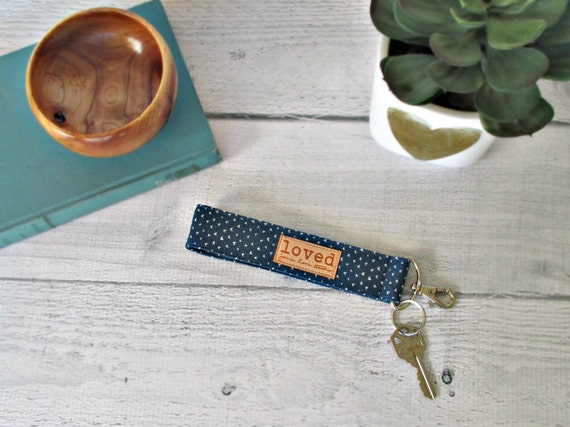 "Key Chain Wristlet. Navy key fob with white hearts and ""loved"" tag."