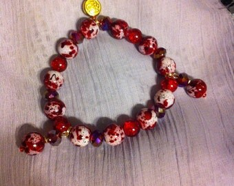 Red mix stretch beaded bracelet, with Celtic knot bead and crystal gold charm.