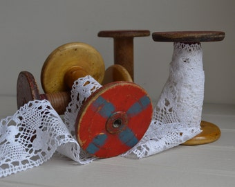 A rustic antique wooden bobbin, red paint to one end.