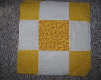 13 finished quilt blocks in the nine patch pattern made with one off white fabric and 2 yellow fabric prints one of them butterflies
