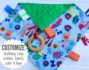 Baby Sensory Tag Blanket | Options: Natural Teething Ring, Crinkle Material, Color | Gray with Blue and Green Comic Book Dogs
