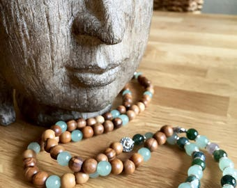 Mala necklace made with moss agate, aventurine and olive wood beads, finished with a crystal quartz