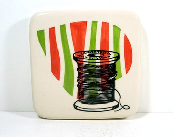 tile with a spool of thread on a somewhat stripey background of red-orange and leaf green. Made to Order.