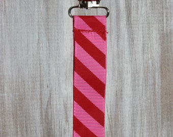 Baby girl pink and red stripe ribbon suspender binky clip