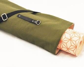 Minimalist khaki yoga mat crossbody bag with black leather tab